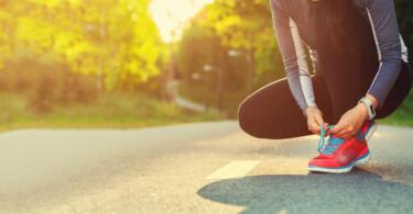 Mitmach-Gesundheit - Joggerin bindet ihre Schuhe