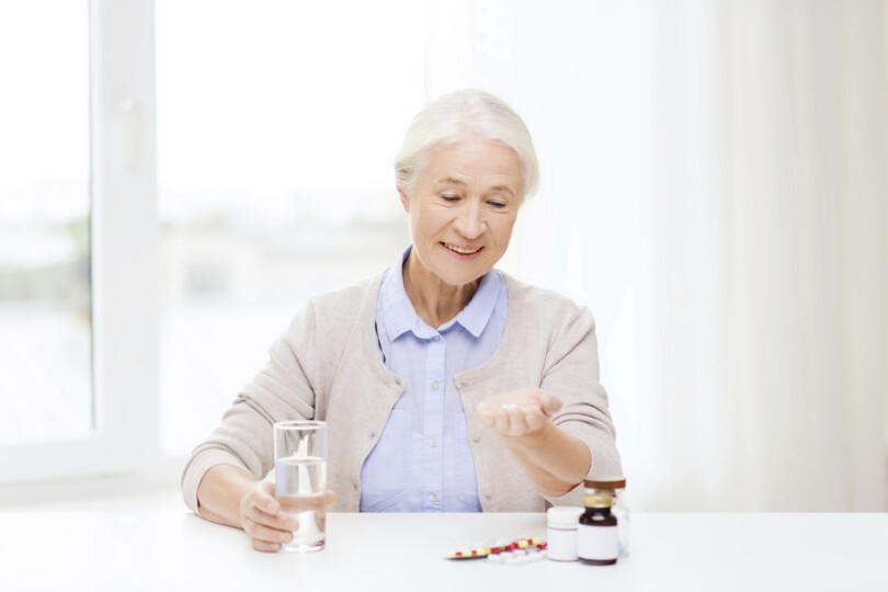 Seniorin nimmt Arzneimittel ein