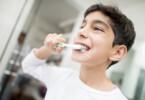 Junge putzt sich mit Zahnpasta die Zähne