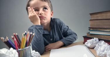 Konzentrationsstörungen bei Kindern - Junge verzweifelt an Hausaufgaben