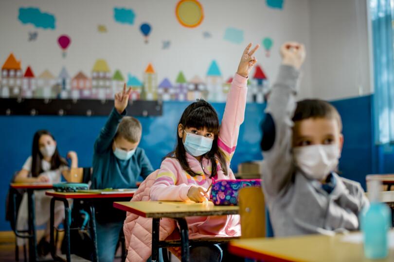 Mundschutz für Kinder - Kind meldet sich in der Klasse