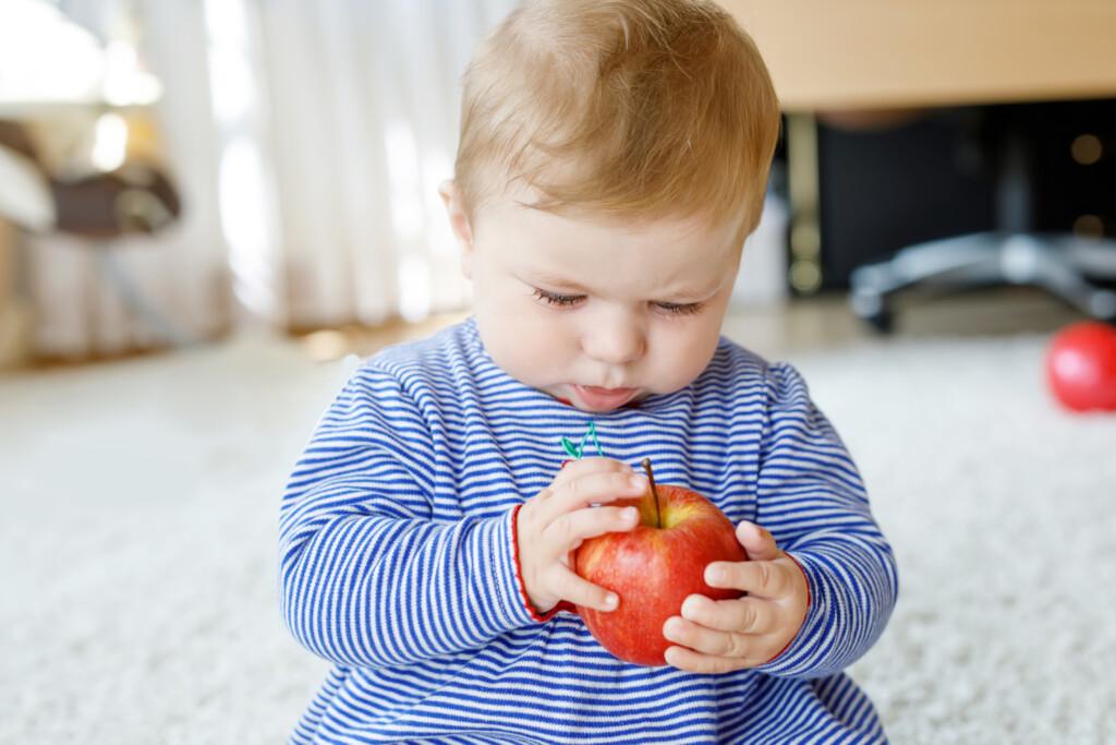 Vitamine für Kinder - Baby mit Apfel