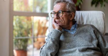 Coronabedingte psychosomatische Erkrankungen - Mann sitzt traurig am Fenster