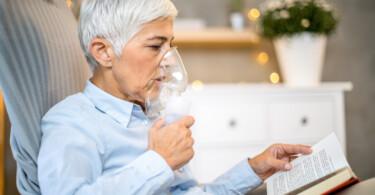 Inhalationsgeräte für die Lokaltherapie bei Atemwegserkrankungen - Frau mit Inhalationsgerät