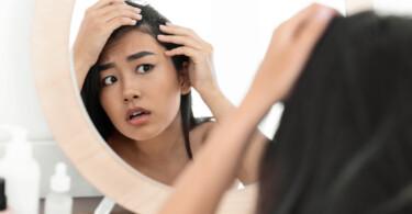 Haarausfall bei Frauen - Frau schaut erschrocken in den Spiegel